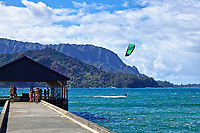"A kite surfer swiftly moves across Hanalei Bay in view of spectators on Hanalei Pier in Kaua'i.  Just below the kite is Mt. Makana, also known as Bali Hai in the epic movie, ""South Pacific."""