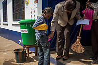 MONROVIA, LIBERIA - FEBRUARY 16: Vice principal, Venoria Crayton, assists 2nd grade student, James Nyema, 9, by tucking away his pink mittens,  after washing his hands in chlorine, at the end of the first day of school, since schools  closed due to the Ebola outbreak 6 months ago, at the C.D.B. King Elementary School on February 16, 2015 in Monrovia, Liberia. Though Ebola cases have receded into the single digits in Liberia, lingering fear and a depressed economy have dampened the turnout at schools. Many have yet to reopen, having failed to meet the minimum requirements put in place to prevent the transmission of the virus. Many of those that have reopened – like C.D.B. King, which, though located in the center of the capital, lacks electricity and running water, and has only a few toilet stalls for a student population that numbered 1,000 before Ebola — are struggling.<br /> Daniel Berehulak for The New York Times