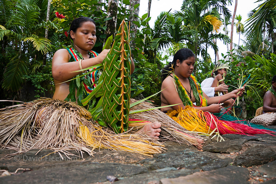 These young girls in traditional outfits are weaving in the village center of Kadai on the island of Yap, Micronesia.
