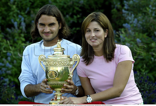 ROGER FEDERER of Switzerland and his girlfriend Miroslava Vavrinec with the trophy after he won the Mens Singles Title, 2003 Wimbledon Tennis Championships, 030706 Photo: Glyn Kirk/actionplus AP1099124...2003 player players man.Grand Slam Grandslam.cup winner win