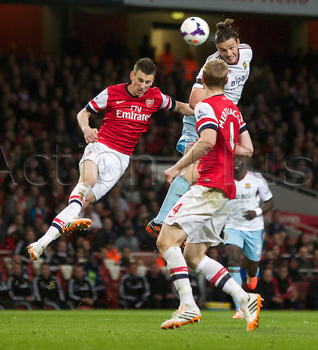 15.04.2014.  London, England. Andy Carroll of West Ham United wins the header against Laurent Koscielny of Arsenal during the Barclays Premier League match between Arsenal and West Ham from the Emirates Stadium.