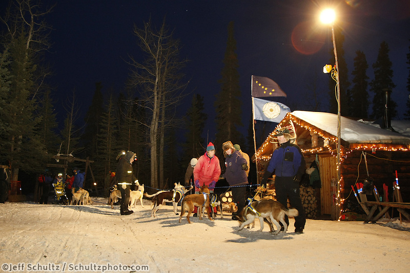 Melissa Owens checks into the Rohn checkpoint on Monday evening.  Volunteer checkers help hold her team and walk them to a parking spot.  Iditarod 2009
