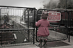 A young girl in a red coat looking through a gate at a steam train