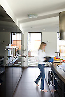 Lisa Maniford photographed preparing a meal in the bright and airy kitchen area of her open-plan contemporary house in Nottingham