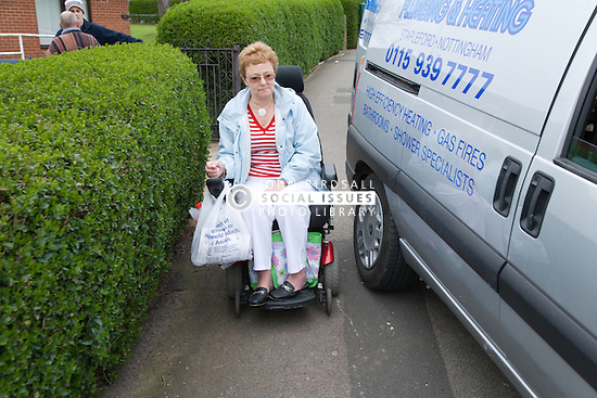 Older woman wheelchair user trying to get past a van parked inconsiderately on the pavement,