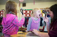 NWA Democrat-Gazette/CHARLIE KAIJO Emily Wilson, 4 (center right), makes a face as Pre-K teacher Laura Thompson (right) holds up a magnifying glass, Monday, February 12, 2018 at Helen R. Walton Children&acirc;&euro;&trade;s Enrichment Center in Bentonville. <br />