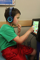 NWA Democrat-Gazette/MARY JORDAN @NWAMARYJ Chandler Mason, 5, of Hiwasse uses a children's iPad to explore learning apps Thursday at the Bentonville Public Library.