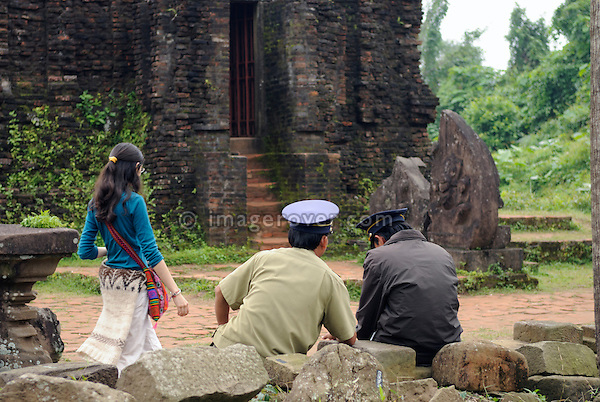 Asia, Vietnam, My Son near Hoi An. Tourist and guards within the temple ruins of group B. Designated a Unesco World Heritage Site, the temple complex of My Son is located in a dense, vegetaded valley beneath Hon Quap or Cat's Tooth Mountain. Having been a religious center from the 4th to the 13th century, today traces of ca. 70 temples may be found, though only about 20 are in good condition. The monuments are divided into 10 groups.