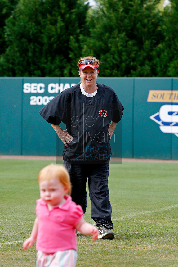 UGA softball coach Lu Harris-Champer plays in the softball stadium with one of her twin daughters, Jenna, on Wednesday, May 17, 2006. Harris-Champer is due to give birth to another daughter early next week.