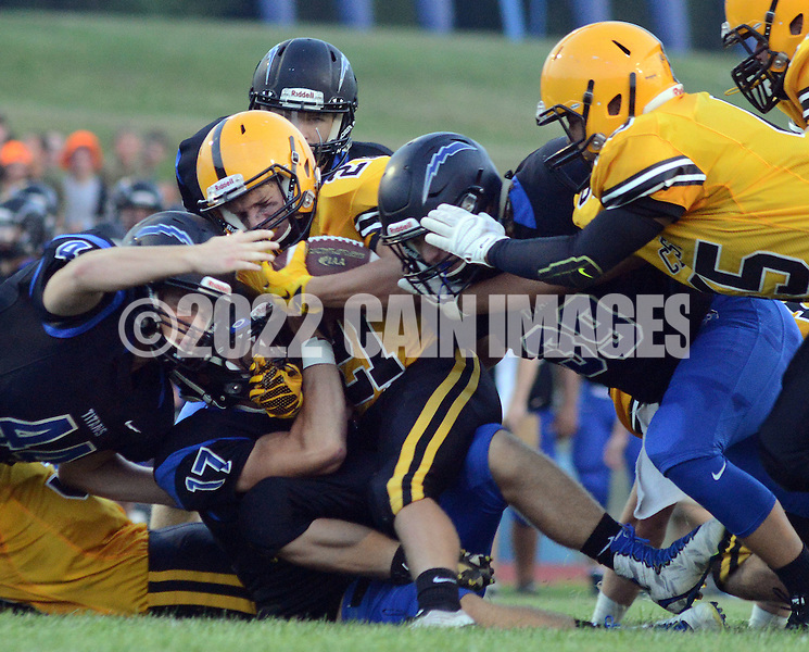 Central Bucks West's Jake Amsler #21 is tackled by Central Bucks South defenders in the first quarter at Central Bucks South Friday September 4, 2015 in Warrington, Pennsylvania.  (Photo by William Thomas Cain)