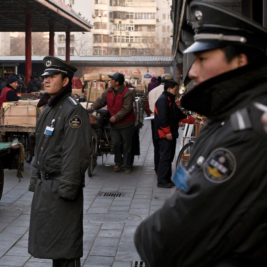Young chinese guards are looking at a customer quarrelling with a seller in the market of Panjiayuan in Beijing.