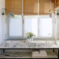 In the bathroom a large double basin of elegant veined marble has a matching shelf beneath it