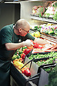 Greengrocer in the produce department arranging red, green and yellow bell peppers in a vegetable display cooler case