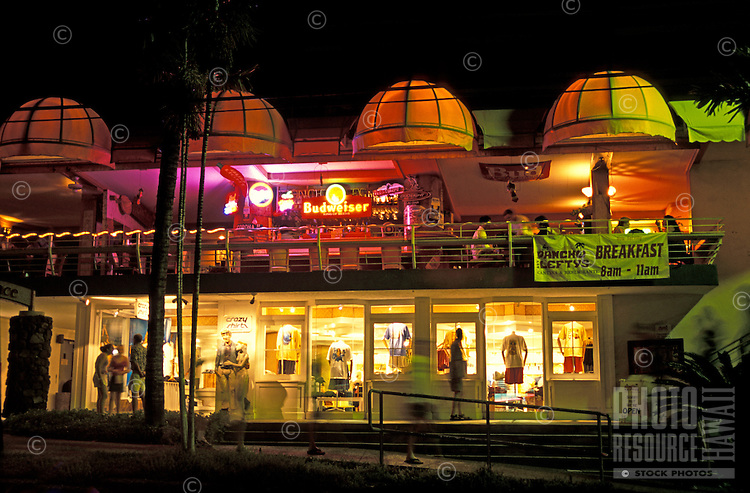 Shoppers head out into the evening to discover the many gift shops, art galleries and restaurants along Front Street  in Historic Downtown Lahaina along the west coast of Maui.