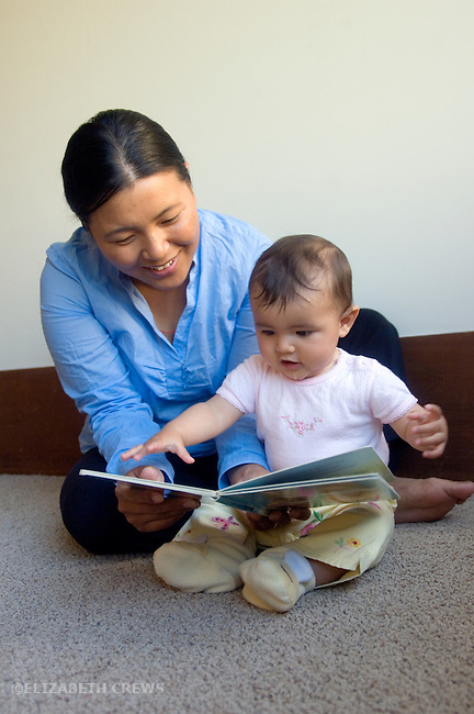 Berkeley CA Nepalese mother and seven-month-old daughter enjoying looking at a book together  MR