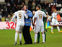 Pictured: Michu of Swansea (9) is held back by a stadium steward during what seems to be a verbal argument with Arsenal goalkeeper Lukasz Fabianski (in green).  Saturday 16 March 2013<br />