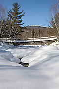 Snow covered foot bridge in the Pemigewasset Wilderness of Lincoln, New Hampshire. This bridge spans the East Branch of the Pemigewasset River along the Thoreau Falls Trail.