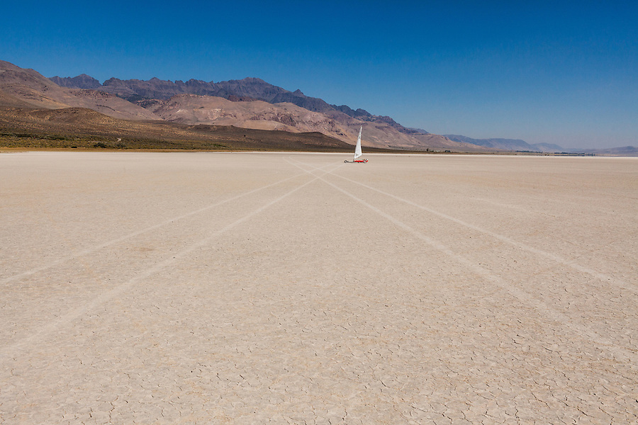 A middle-aged man steers his landsailer across the dry playa of the Alvord Desert in Southeast Oregon.