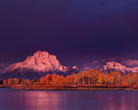 749450328 dawn lights up mount moran and the teton range during a clearing storm and highlights the fall colored aspens along the oxbow bend of the snake river in grand tetons national park wyoming