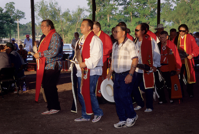 Miami Potawatomi tribal pow wow and gathering of men gourd dancers wearing traditional red vestments, Oklahoma