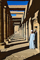 Two Egyptian men and colums casting shadows, Temple of Philae, on Agilika, an island in the Nile River, near Aswan, Egypt.