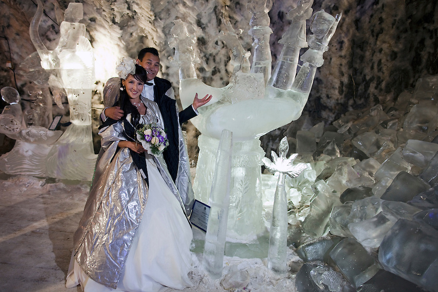 Yakutsk, Yakutia, Russia, 19/08/2011..Newly-weds Nadezhda and Vasily Fedorov inside the Permafrost Kingdom, an underground tourist attraction inspired by the extreme cold of Yakutia. The 150 metre deep complex of tunnels in the Russian permafrost are decorated with ice sculptures, a wolf-fur covered throne, an office complete with the coolest computer and telephone, a children's slide and other ingenious creations - all hewn from blocks of ice.