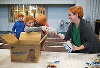 NWA Democrat-Gazette/CHARLIE KAIJO Daniel Lane of Fayetteville and daughter Willow Lane, 9 (left), box MannaPack meals as Brandi Lane (right) helps, Sunday, March 4, 2018 at The Jones Center in Springdale.<br /><br />Tacos 4 Life and Feed My Starving Children hosted their first NWA MobilePack of the year. Nearly 1,000 volunteers worked together throughout the three days to pack MannaPack meals that Tacos 4 LifeÕs guests have raised for the past several months.