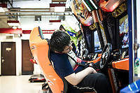 "A Chinese boy takes a rest as he plays videogames in a game room in WangFuJin District in Beijing, China, July 19, 2014. <br /> <br /> This image is part of the series ""24/7"", an ironic view on restless and fast-growing Chinese economy described through street vendors and workers sleeping during their commercial daily activity.<br /> <br /> © Giorgio Perottino"