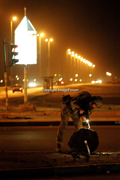Members of The Staffordshire Regiment check for danger as they carry out a night patrol on the streets of Al Amarah in the Maysan Province, north of Basra, in the early hours of 13 October 2005, just days ahead of the constitutional referendum on 15 October. Three Staffordshire Regiment soldiers were killed by a roadside bomb in Al Amarah in July. AFP PHOTO / JOHN D MCHUGH