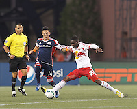 New England Revolution midfielder Diego Fagundez (14) works to clear ball as New York Red Bulls midfielder Lloyd Sam (10) challenges. In a Major League Soccer (MLS) match, the New England Revolution (blue) tied New York Red Bulls (white), 1-1, at Gillette Stadium on May 11, 2013.