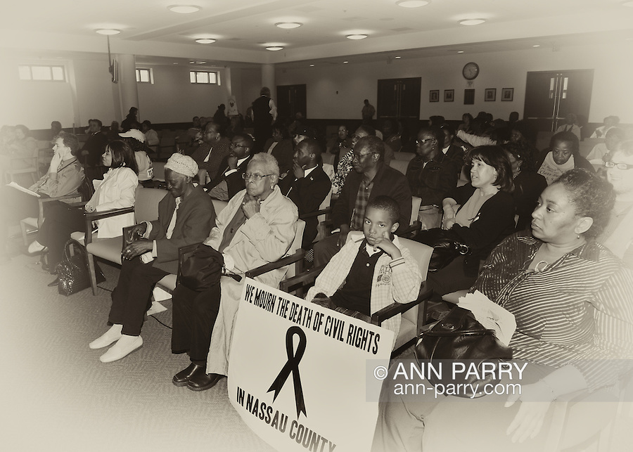 "May 9, 2011 - MINEOLA, NY:  Amid adults at public hearing, young Ramel Smith, Jr., sitting with sign: ""We Mourn the Death of Civil Rights in Nassau County."" Front row, fourth from right, is Golena White of Hempstead. Nassau County Legislature's public hearing on Legislative Redistricting, at Nassau County Executive and Legislative Building, 1550 Franklin Avenue, Mineola, Long Island, New York, USA."