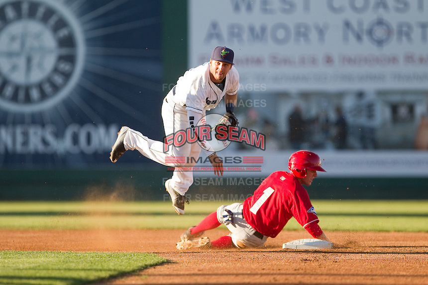 Jordan Cowan (3) of the Everett Aquasox hops over the slide of Andrew Guillotte (1) of the Vancouver Canadians during a game at Everett Memorial Stadium in Everett, Washington on July 27, 2015.  Everett defeated Vancouver 6-0. (Ronnie Allen/Four Seam Images)