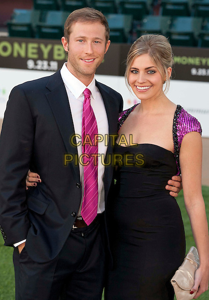 """Casey Bond & guest.""""Moneyball"""" Premiere held at The Paramount Theatre, Oakland, California, USA..September 19th, 2011.half length black suit jacket dress pink tie.CAP/ADM/DA.©Drew Altizer/AdMedia/Capital Pictures."""