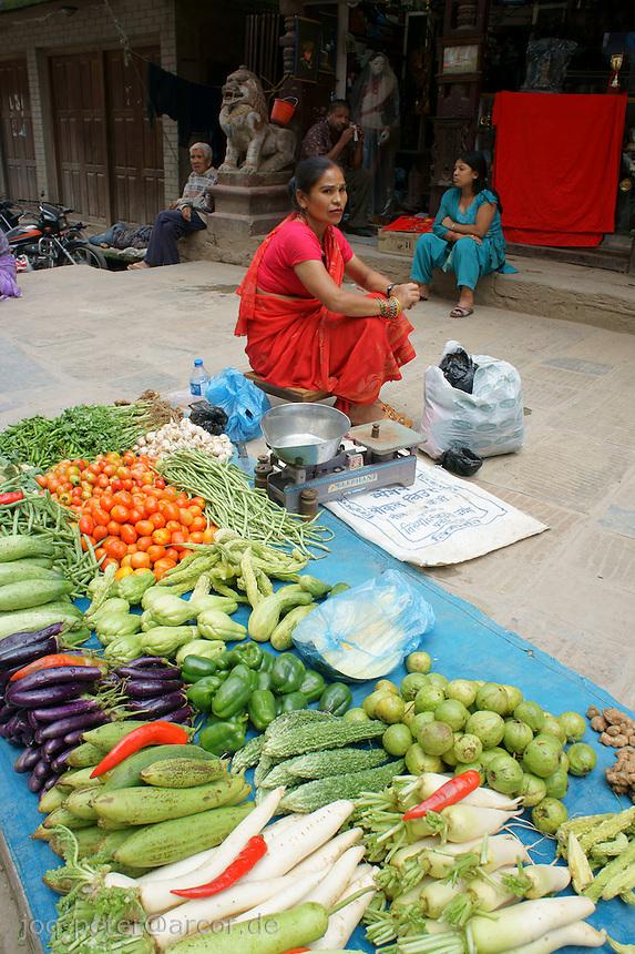 woman in red dress selling vegetable in the streets of Kathmandu, Nepal