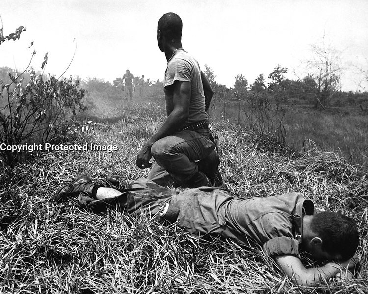 A young American lieutenant, his leg burned by an exploding Viet Cong white phosphorus booby trap, is treated by a medic.  1966.  JUSPAO.  (USIA)<br /> EXACT DATE SHOT UNKNOWN<br /> NARA FILE #:  306-MVP-16-1<br /> WAR &amp; CONFLICT BOOK #:  404