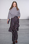 "Model Anja walks runway in a boiled wool raglan sleeve sweater in light grey and wool striped wrap skirt over matching trouser, from the Vivienne Tam Fall Winter 2016 ""Cultural Dreamland The New Silk Road"" collection, presented at NYFW: The Shows Fall 2016, during New York Fashion Week Fall 2016."