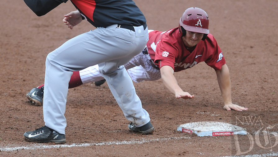 NWA Democrat-Gazette/ J.T. WAMPLER -- Arkansas' Joe Serrano jumps back to first base to avoid the pick of throw to against Southeast Missouri State's Ryan Rippee March 18, 2015.