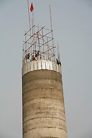 Workers build a chimney at a factory in Linfen, Shanxi Province, China. A survey from China's State Environmental Protection Agency shows that the province of Shanxi has the top three cities with the worst air pollution in China, with the city of Linfen topping the list from its numerous coking and steel factories..15 Oct 2006