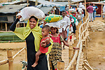 Carrying emergency shelter materials and food, Rohingya refugees cross a rickety foot bridge in the sprawling Kutupalong Refugee Camp near Cox's Bazar, Bangladesh. More than 600,000 Rohingya refugees have fled government-sanctioned violence in Myanmar for safety in this and other camps in Bangladesh.