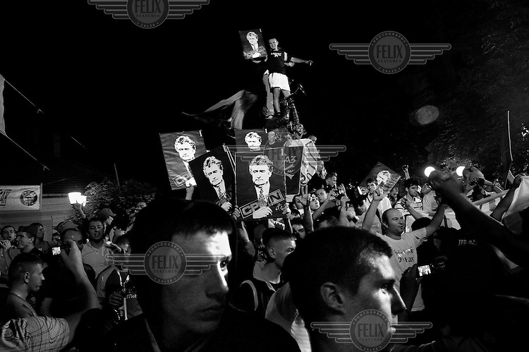 Members of the Serb nationalist group Obraz hold aloft pictures of Bosnian Serb politician Radovan Karadzic during a demonstration in the main square at Guca during the trumpet festival.