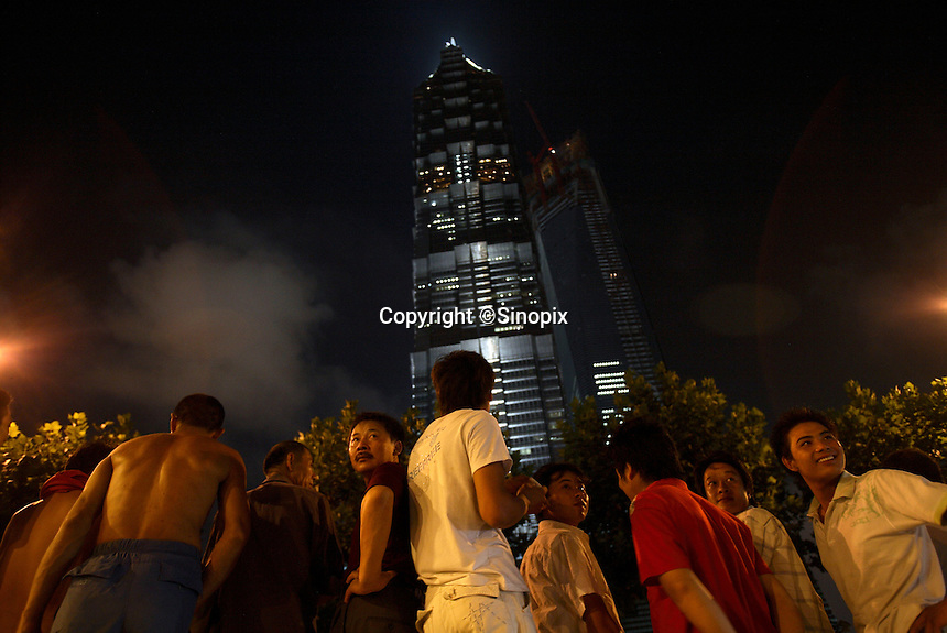 A group of migrant workers stand in front of the Jin Mao Tower in Shanghai, China..24 Aug 2007