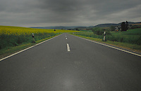 yellow oilseed rape,Empty country road on a grey cloudy day with hills in the back ground. Yellow oil seed rape crop on the left open countryside and homes on the right. Aschaffenburg area, Bavaria, Germany.