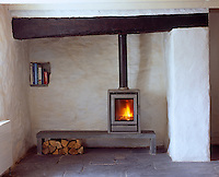 A contemporary wood burning stove sits on a low slate bench in this otherwise traditional cottage living room