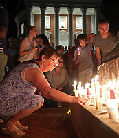 Kris Bean places a candle at the foot of the Thomas Jefferson Statue after thousands of UVa students, faculty and Charlottesville residents led a candle light march across grounds Wednesday night in Charlottesville, Va. The march was an effort to stomp out the hate across campus from last Friday's torch march. Photo/Andrew Shurtleff