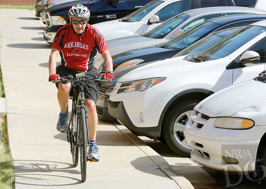 NWA Democrat-Gazette/DAVID GOTTSCHALK  Dan Ferritor, the new interim University of Arkansas Chancellor, arrives by bicycle on the campus in Fayetteville Friday, August 7, 2015.  Ferritor, an avid cyclist, plans to ride to work three days a week.