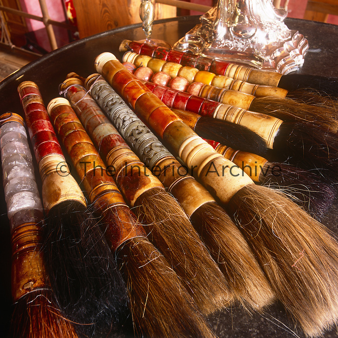 A collection of Chinese paint brushes with decorative bone handles arranged on a table.
