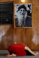 Wasco, Oregon, January 1984: A disciple meditating under the portrait of Bhagwan Rajneesh hanging on the wall. Rajneeshpuram, was an intentional community in Wasco County, Oregon, briefly incorporated as a city in the 1980s, which was populated with followers of the spiritual teacher Osho, then known as Bhagwan Shree Rajneesh. The community was developed by turning a ranch from an empty rural property into a city complete with typical urban infrastructure, with population of about 7000 followers.