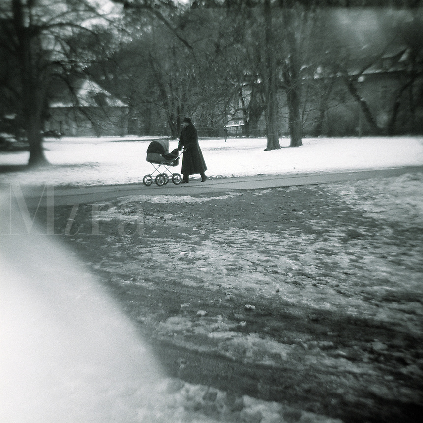 Woman with baby carriage walking in the snow.