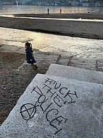 "Switzerland. Canton Ticino. Lugano. View on Lake Lugano and the city. A young asian girl is running near the lake. A political graffiti is written on the granite ground "" Fuck the police"". Lake Lugano (Italian: Lago di Lugano or Ceresio) is a glacial lake. 26.01.2019 © 2019 Didier Ruef"