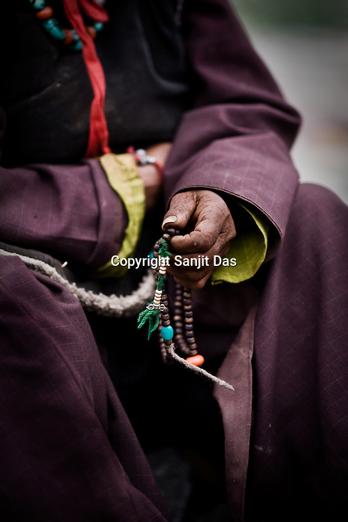 """A local villager is seen with prayer beads while waiting for His Holiness the Twelfth Gyalwang Drukpa, the head of the Drukpa Lineage to arrive in the outskirts of Hemis in Shwang. """"Walking On The World's Rooftop"""" Pad Yatra from Manali to Ladakh, of 400kms was focused at raising awareness awareness of His Holiness' charitable projects including education , environment and cultural preservation of tribal people from the area. Accompanied on the Yatra by large numbers of Buddhist monks, nuns, foreigners and local villagers. The culmination of the Pad Yatra coincides with the colourful age-old Hemis festival in Leh, Ladakh, India."""